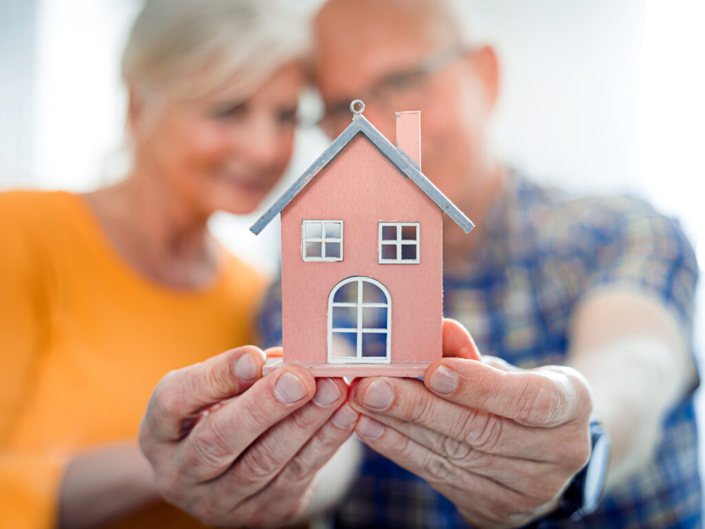 Two people holding up a house to represent senior living